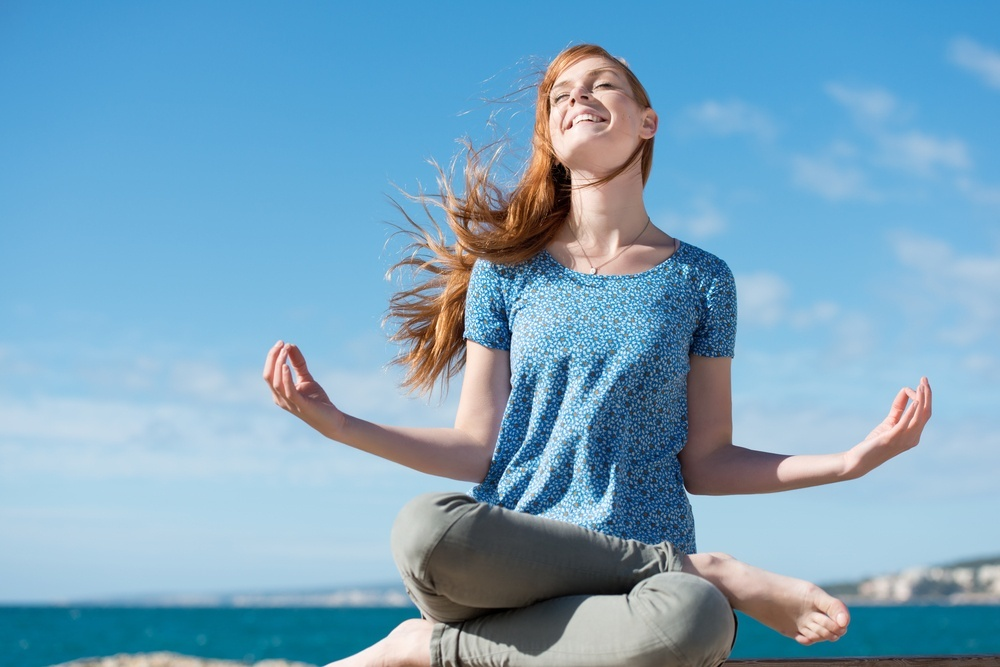 Beautiful woman meditating at the seaside sitting cross-legged on the rocks with her head tilted to the sun and her eyes closed in ecstasy