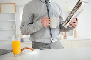 Businessman holding a newspaper while having breakfast in his kitchen