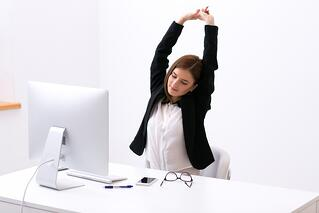 Businesswoman sitting at the table in office and stretching her hands above her head.jpeg