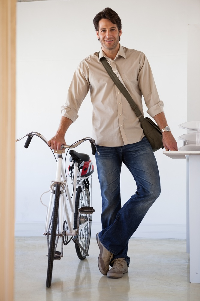 Casual businessman standing with his bike smiling at camera in the office.jpeg