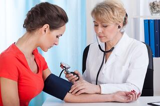 Doctor taking blood pressure of female patient at office.jpeg