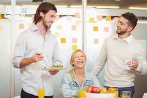 Employees having fun during breakfast in creative office