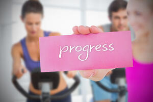 Fit blonde holding card saying progress against fitness class in gym