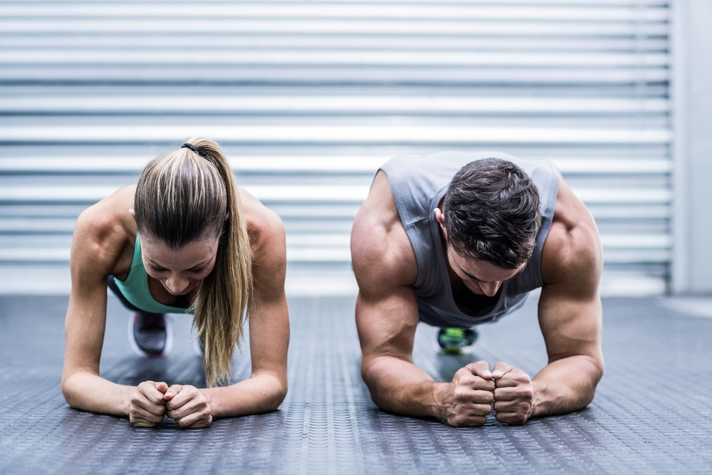 Front view of a muscular couple doing planking exercises.jpeg