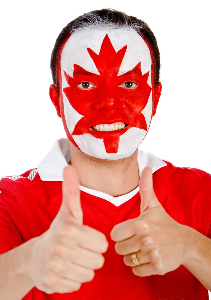 Happy Canadian man with the flag painted on his face and thumbs up- isolated.jpeg