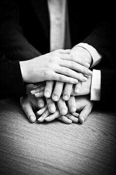 Image of business partners hands on top of each other symbolizing companionship and unity-1