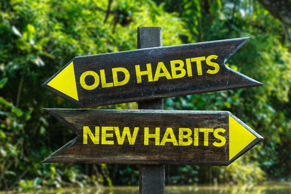 Old Habits - New Habits signpost with forest background