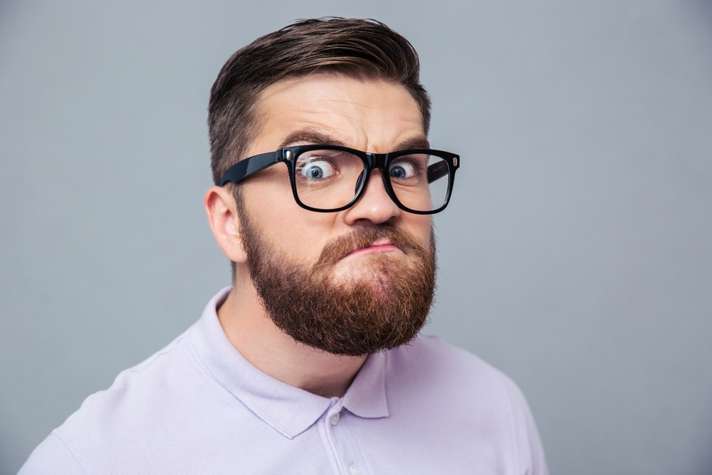 Portrait of a funny hipster man looking at camera over gray background.jpeg