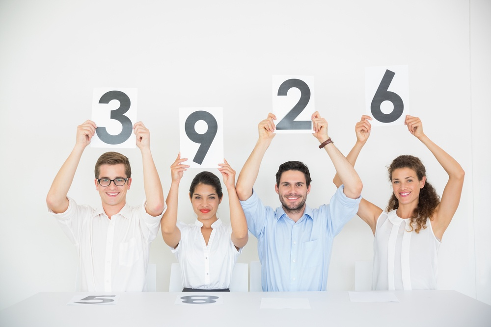 Portrait of panel judges holding score signs in office.jpeg