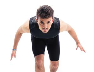 Sports man getting ready to run isolated on a white background. Looking at camera