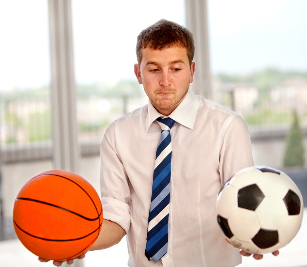 Undecided business man between basketball or football.jpeg