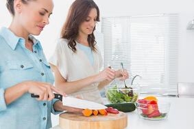 Women preparing salad together  in the kitchen