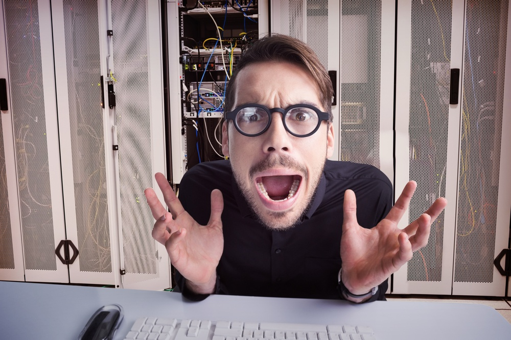 Worried businessman with glasses using computer against data center.jpeg