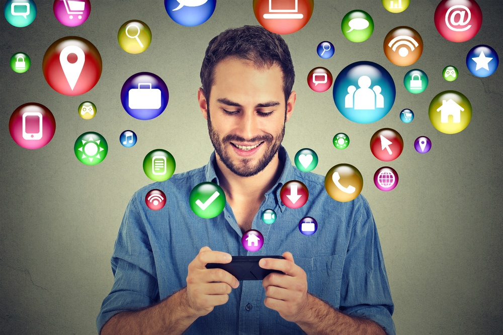 communication technology mobile phone high tech concept. Happy man using texting on smartphone social media application icons flying out of cellphone isolated grey wall background. 4g data plan.jpeg