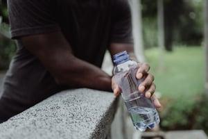 Hand Holding Water Bottle Outside
