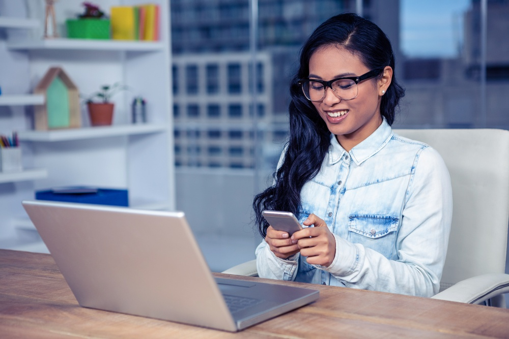 Smiling Asian woman with eyeglasses using smartphone in office-1.jpeg