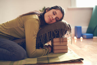 Attractive mixed race woman doing restorative yoga-1