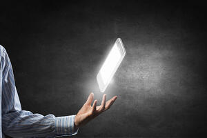 Businessman holding in hand glowing mobile phone on dark background
