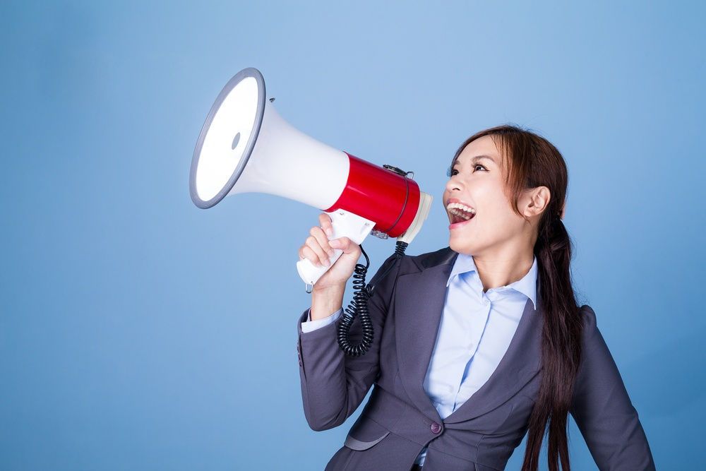 Businesswoman making announcement with megaphone.jpeg