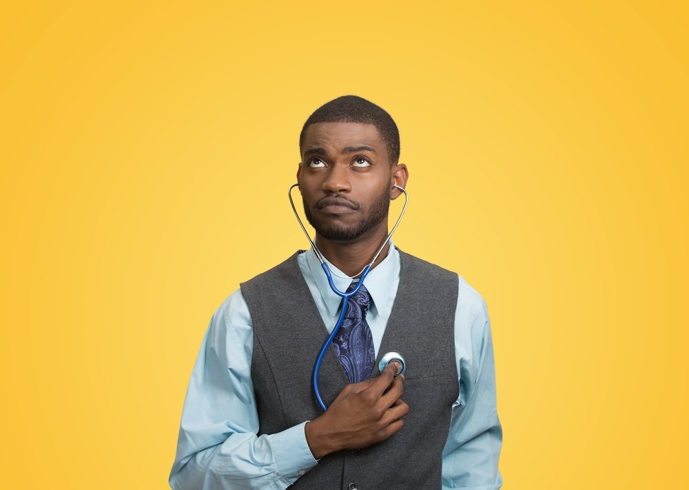 Closeup portrait executive man, business person, worker listening to his heart with stethoscope looking up isolated yellow background. Preventive medicine, financial condition concept. Face expression.jpeg