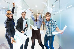 Group of joyful excited business people throwing papers and having fun in office-3