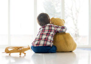 Little child sitting in living room with teddy bear-1