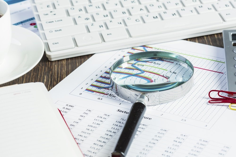 Magnifing glass and documents with analytics data lying on table.jpeg