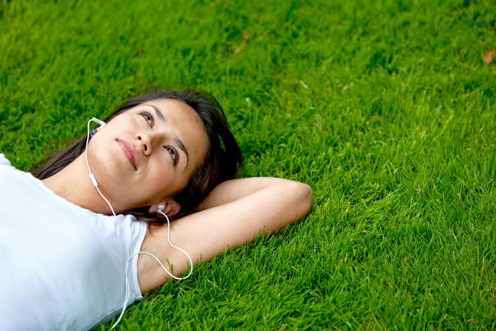 Pensive woman lying on grass listening to music outdoors