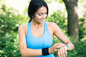 Smiling sporty woman in headphones using smart watch outdoors in park-1