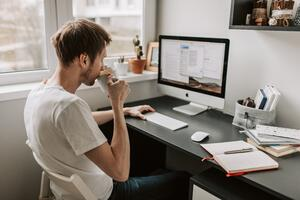 man sipping coffee at desk