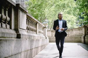 Man in suit walking in park on phone