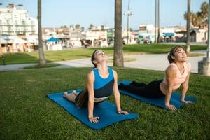 Two people doing outdoor yoga